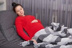 La femelle enceinte avec le grand ventre, utilise le chandail rouge, dort au sofa, couvert de plaid, apprécie l'atmosphère domest photographie stock