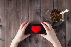 La femelle envoient le coeur par des sms Images stock