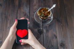 La femelle envoient le coeur par des sms Image stock