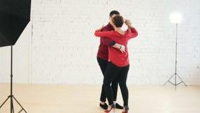 La femelle et le jeune homme de Moyen Âge dans la chemise rouge danse le kizomba dans le studio banque de vidéos