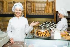 La femelle fait cuire avec du pain frais et savoureux dans la boulangerie Images stock