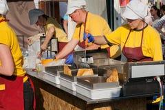 La femelle fait cuire dans l'uniforme du restaurant de prêt-à-manger faisant cuire la nourriture frite Images libres de droits