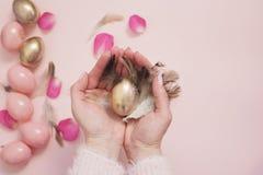 La femelle, femme remet tenir un oeuf de pâques Rose et oeufs de pâques d'or Concept en pastel de Pâques avec des oeufs, des fleu Photographie stock libre de droits