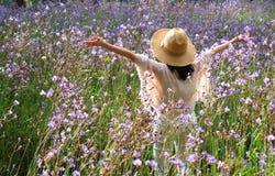 La femelle heureuse soulevant ses bras apprécient la lumière du soleil de matin parmi le beau gisement de fleur pourpre Image libre de droits