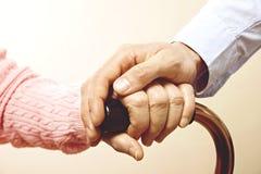 La femelle mûre à l'établissement de soins plus âgé obtient l'aide de l'infirmière de personnel d'hôpital Fermez-vous des mains f Images libres de droits