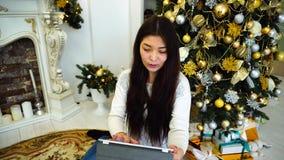 La femelle mignonne à l'aide de la Tablette fait des cadeaux de commande en ligne et se reposer sur l'arbre de Noël décoré par fo clips vidéos