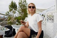 La femelle moderne dans des lunettes de soleil à la mode utilise le téléphone de cellules pendant le repos en café dehors photos stock