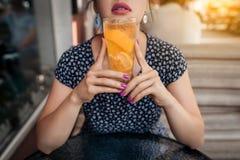 La femelle prend le déjeuner avec le cocktail froid de limonade, Images libres de droits