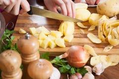 La femelle remet des pommes de terre de découpage Photos stock