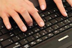 la femelle remet l'ordinateur portatif de clavier images libres de droits