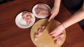 La femelle remet le chef coupant le sein cru de viande de poulet banque de vidéos