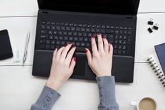 la femelle remet le fonctionnement d'ordinateur portatif Bureau de bureau sur le fond blanc photos libres de droits