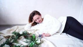 La femelle renversante correspondent dans les réseaux sociaux utilisant le smartphone, se trouvant sur le plancher sur le plaid à banque de vidéos