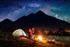 La femelle s'asseyant près de la tente et fait la photo du ciel étoilé Photographie stock libre de droits