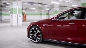 La femelle s'assied dans la voiture rouge mettant la tête sur la roue quand l'autre voiture s'arrête par dans le garage banque de vidéos