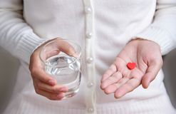 La femelle tient la pilule rouge dans la forme de coeur Photo stock