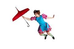 La femelle vole sur un parapluie rouge image stock