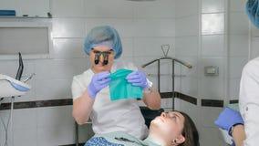 La femme à la clinique de dentiste obtient le traitement dentaire pour remplir cavité dans une dent Restauration et matériau comp photographie stock