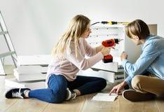 La femme à l'aide du foret électronique installent le coffret Image libre de droits