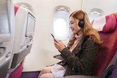 La femme ? l'aide du smartphone et ?coutant la musique avec des ?couteurs sur l'avion chronom?trent en vol photos stock