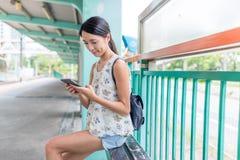 La femme à l'aide du téléphone portable et attendant des amis dans le rail léger s'exercent Photos libres de droits