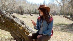 La femme à la mode attrape le signal à son téléphone portable tout en recherchant les endroits intéressants en montagnes, 20s 4k banque de vidéos