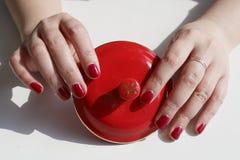 La femme à la mode a peint le vernis à ongles rouge, main, deux mains tenant une couverture rouge de tasse de thé Photographie stock