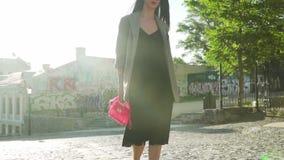 La femme à la mode avec la promenade rose élégante de sac dans le mouvement lent en soleil rayonne banque de vidéos