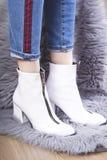 La femme à la mode portent les bottines blanches et la position sur la couverture velue photos stock