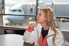 La femme à un hublot et à l'avion sur le fond Photographie stock