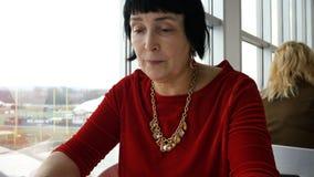 La femme âgée élégante, appartenance ethnique caucasienne, lit le menu banque de vidéos