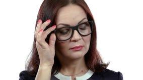 La femme âgée par milieu avec des lunettes flirte dans l'embarras Fond blanc banque de vidéos