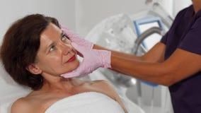 La femme âgée par milieu l'obligeant à peler a examiné par le dermatologue clips vidéos