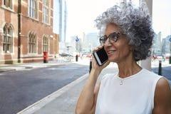 La femme âgée par milieu parlant au téléphone dans la rue de ville, se ferment  photo stock