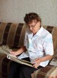 La femme âgée seule regarde un album d'illustration de famille Images libres de droits