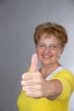 La femme âgée sourit avec le pouce vers le haut Photos libres de droits