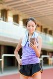 La femme écoutent la musique avec le téléphone portable en stade de sport Photographie stock
