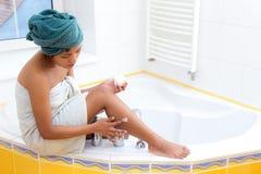 La femme écrème sa jambe Image libre de droits