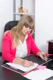 La femme écrit dans un dossier Image stock