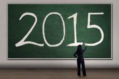 La femme écrit le numéro 2015 sur le tableau noir Images libres de droits