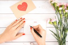 La femme écrit la lettre d'amour sur le livre blanc avec la figue rouge de forme de coeur Image libre de droits