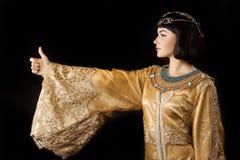 La femme égyptienne heureuse aiment Cléopâtre avec des pouces vers le haut de geste, sur le fond noir Image libre de droits