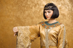 La femme égyptienne sérieuse aiment Cléopâtre avec des pouces font des gestes vers le bas, sur le fond d'or Images libres de droits