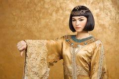La femme égyptienne sérieuse aiment Cléopâtre avec des pouces font des gestes vers le bas, sur le fond d'or Images stock