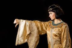 La femme égyptienne sérieuse aiment Cléopâtre avec des pouces font des gestes vers le bas, sur le fond noir Photo libre de droits