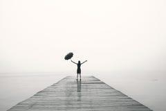 La femme élégante dans le noir se réjouit avec leurs bras sous la pluie photos libres de droits