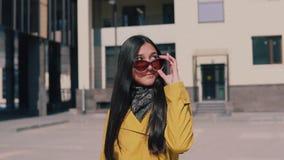 La femme élégante dans un imperméable jaune avec de longs cheveux foncés va avec le bagage enlève des verres regardant autour et  banque de vidéos