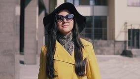 La femme élégante en chapeau jaune et verres d'imperméable va de pair avec le bagage et le sourire banque de vidéos