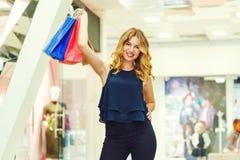 La femme élégante heureuse avec des paniers regarde l'appareil-photo et sourit tout en faisant l'achat dans le mail Image libre de droits