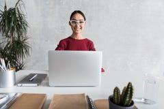 La femme élégante joyeuse travaille dans le bureau Photographie stock libre de droits